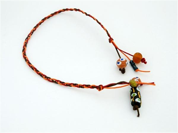 Bookmark made from plaited leather thonging and African beads.