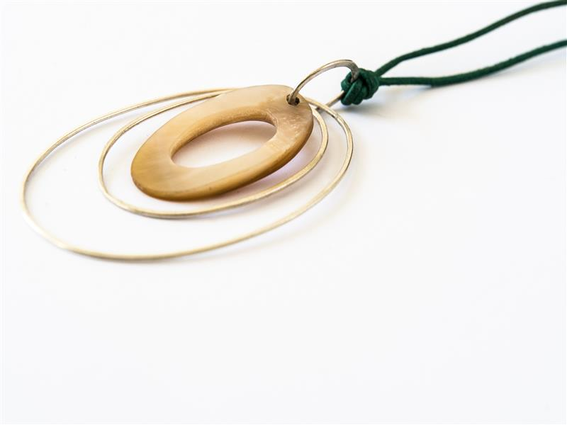 Pendant with thonging to enable the wearer to adjust the length.