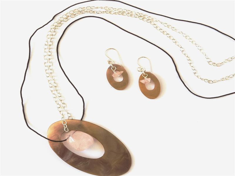 Large mother of pearl motif, on sterling silver chain and leather thonging, with complimentary earrings.  Both decorated with rose quartz gems.