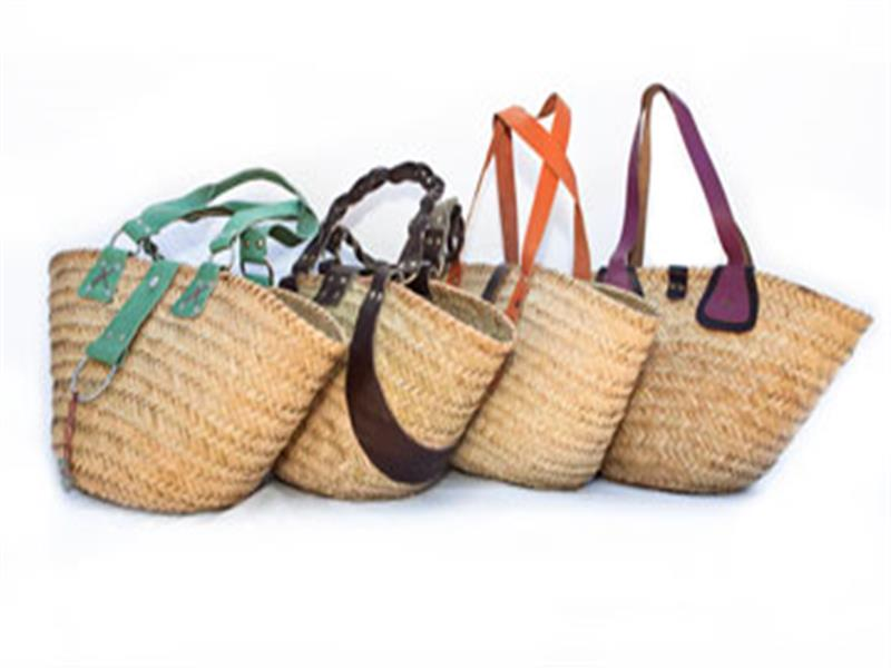 Featured front of shot: palm leaf basket with hand thonged leather handle and recycled glass or ceramic hand-painted African beads on a chrome ring decorat...
