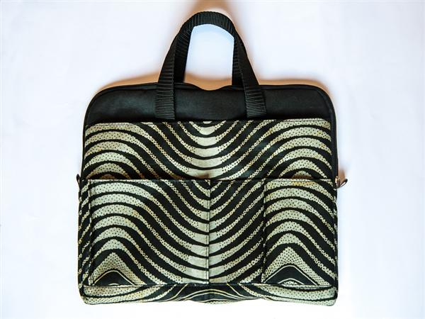 Computer bag with internal and external portfolio, phone and pen pockets, detachable shoulder strap.  Available in canvas or patterned kitenge. 43 x 33 cm....