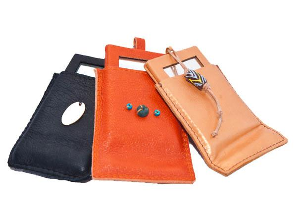 Leather bound make up mirror, in pouch, decorated with shell, cow horn or African beads.
